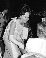 Leslie Caron bending down and smiling.