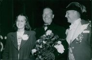 Maurice Auguste Chevalier standing with man and a woman and smiling.