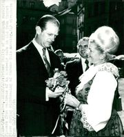 Prince Philip receives flowers by a woman waitress at a cafe during her tour of Warsaw