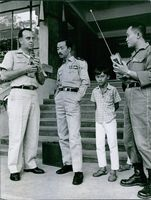 Nguyễn Cao Kỳ looking a the radio the American officer is holding. his son and another military officer stands in the background.
