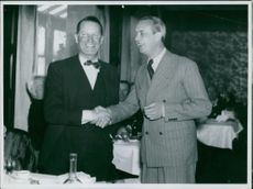 Maurice Auguste Chevalier shaking hand with a man.