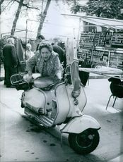 Elsa Maxwell posing with scooter in Paris.