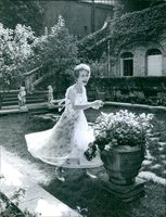 Gisèle Pascal  a French actress smiles while walking in the garden, 1961.