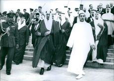 King Saud walking with group of people.
