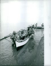 Soldiers sitting in boat in water.