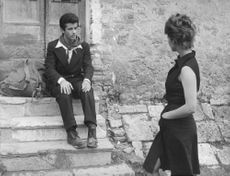 Claudia Cardinale looking at man sitting on stair.
