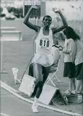 Abdi Bile photographed with his arms raised while running at the track and field. 1987.