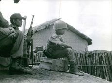 A little boy in uniform , sitting, with other soldiers behind him, in Vietnam