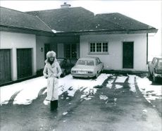 Woman walking beside house, while snow falling.