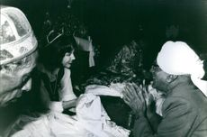 Hope Cooke holding a cloth while talking to a man inside the palace.