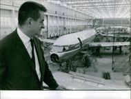 1962  A photo of a man standing in the aircraft manufacturing plant.
