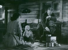 A scene from the film Bara en mor, Eva Dahlbeck sitting on the floor with a girl and Åke Fridell sitting on a long chair, 1949.
