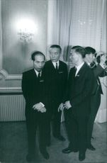 A photo of Vietnam's President Ho Chi Minh (left) standing while  listening.