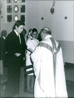 Royal couple, Prince Michel and Béatrice solemnly bowing their heads in front of a Clergy.