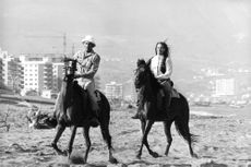 Leigh Taylor-Young riding horse with a man.