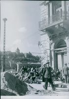 People gathered outside while siting in front of building in Hungary during World War II, 1946.