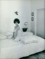 Irina Demich sitting on bed.