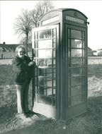 A woman standing beside of phone box.