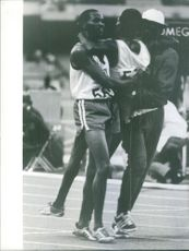 Athlete being supported by two other athletes.