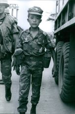A child wearing uniform and looking towards the camera.1968