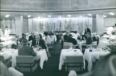 A group of people eating in restaurant 1953.