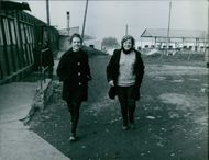 Two Women walking together.