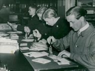 Four post officials stamp the new stamps at the Post Office
