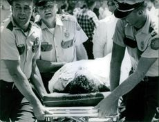 An injured man carried on stretcher by guards.