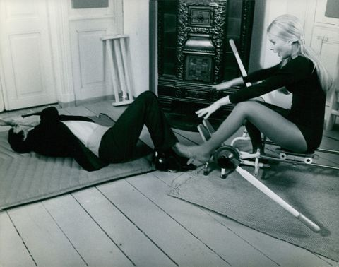 Pamela Tiffin sitting on an exercise equipment while the man lay on the floor.