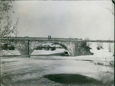View of a bridge, soldiers walking on it while communicating with each other.