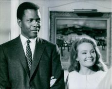 Sidney Poitier with a woman standing in a event.