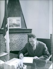 Ferhat Abbas sitting and reading a paper.