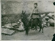 Soldiers riding a donkey in the street during Tyskland war, 1914.