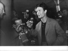 Jacques Charrier, holding a wine glass and chatting with another man, is surrounded by media men.