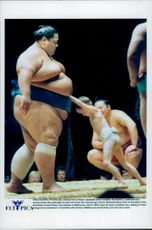 Japanese summons Konishiki is waiting to be relegated by a school boy during the Grand Sumo Tournament.