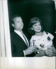 Rhonda Fleming and a man on her side holds a glass and looks at something from a distant .