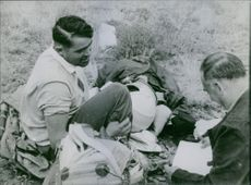 Two men sitting on ground.