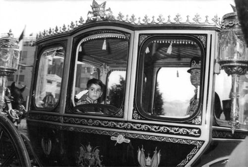 The king and his son inside a vihicle, watching through the window.