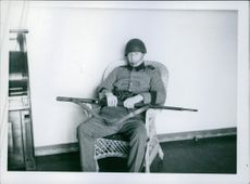 A soldier sitting on the chair, with his rifle gun.