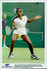 Venus Williams fires the ball to opponent Grzybowska during the tennis tournament Wimbledon Championship.