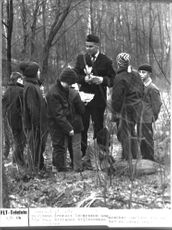 A group of young 'detective story' of one of Gothenburg Blomkvist clubs help police officer Lennart Andersson investigate a wooded area.