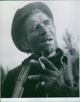 A man holding a a cigarette between his fingers, 1944.