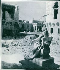 Malta La Valeta  undamage statue of woman siiting on a concrete chair and surrounded by rabbled buildings as war damade in Malta.