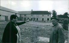 A woman pointing her finger at the building with a man standing beside her.