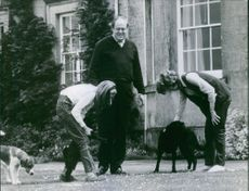 Arthur Christopher John Soames with family members playing with their dogs.