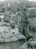 Soldier guarding and people sitting beside in Vietnam.