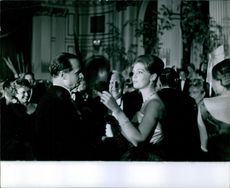 A man looking at Princess Birgitta of Sweden and Hohenzollern at a party.