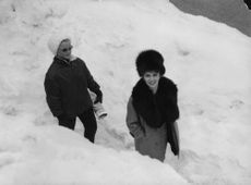 Gina Lollobrigida walking ahead of another woman, in snow.