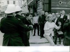 A woman run and the man captured by cop while the people looking at them.1964.