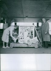 Woman putting bouquet of flowers in a transporter in a market hall in 1941.